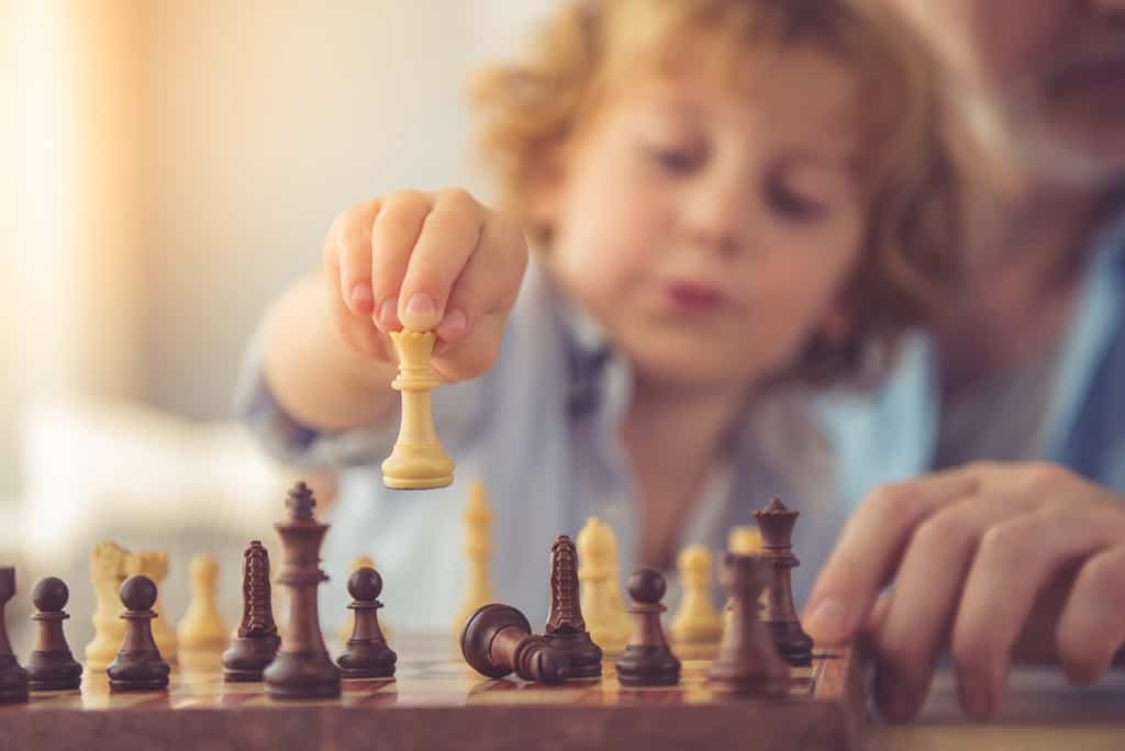 A young child plays chess