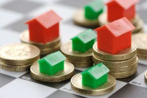 Monopoly houses and hotels on stacked pound coins to show the change in stamp duty for first time buyers