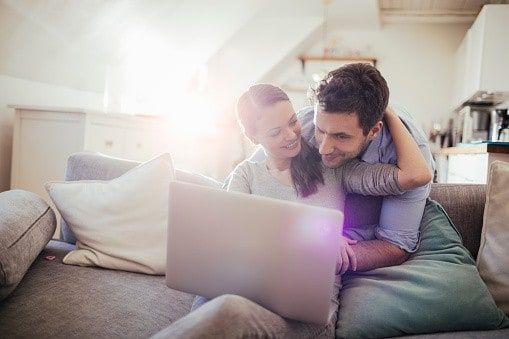 A man and woman embrace as they look at a laptop together and decide to remortgage