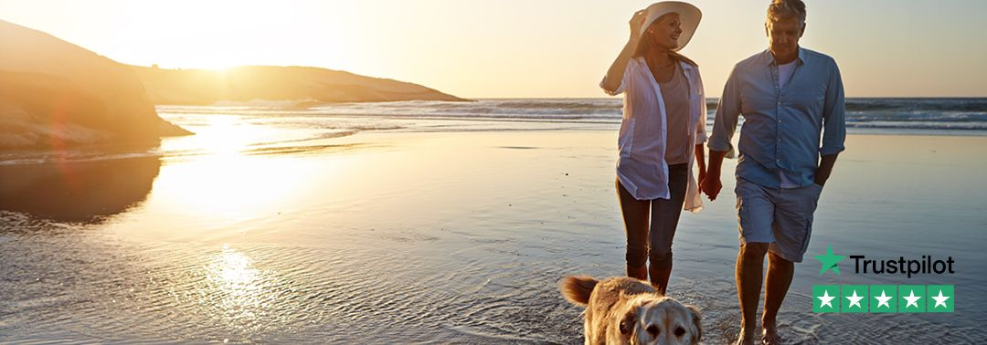 Older couple and a dog enjoy walk on the beach after releasing equity in their home